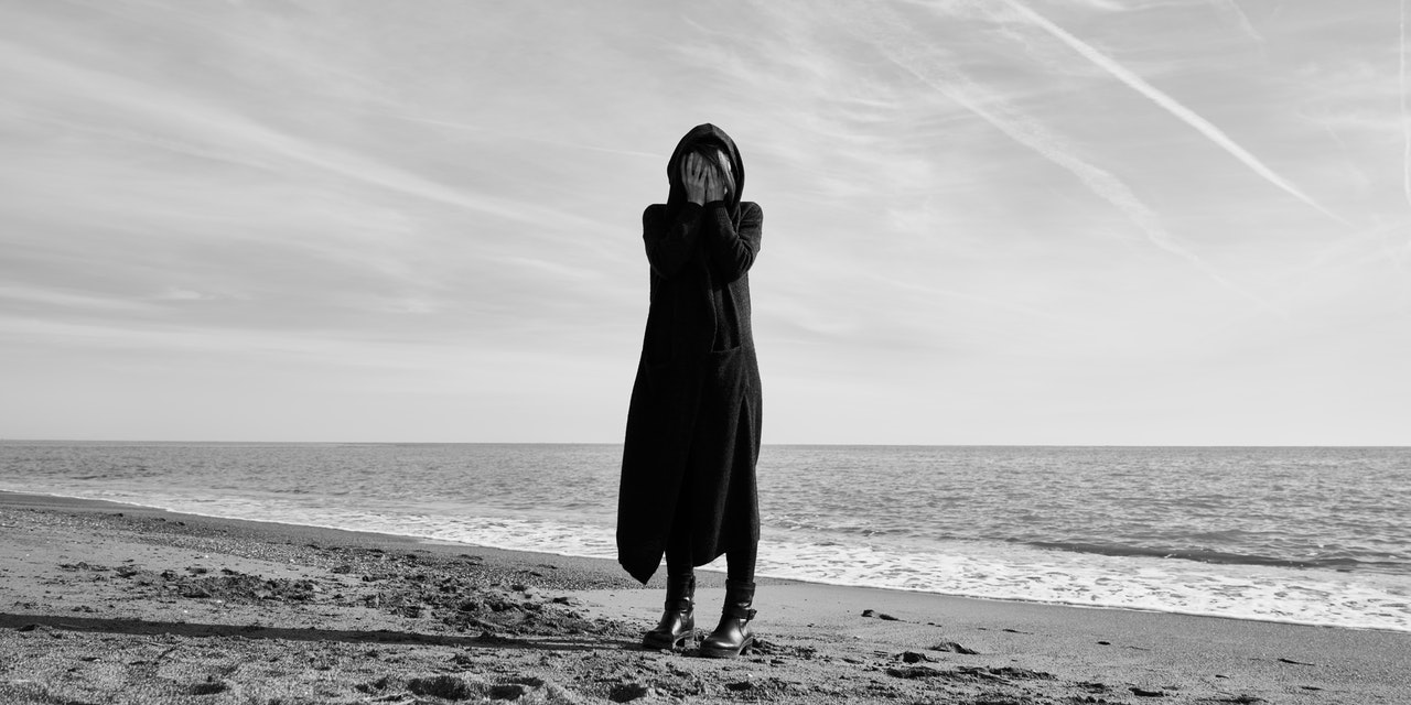 woman standing on the beach, dressed in black, with hands covering her face. black and white photo.