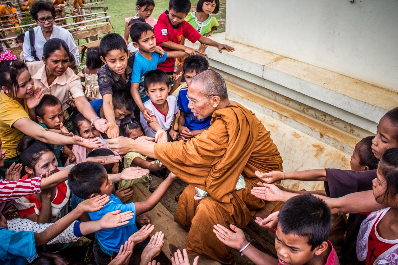 Monk surrounded by children, all with their hands outstretched