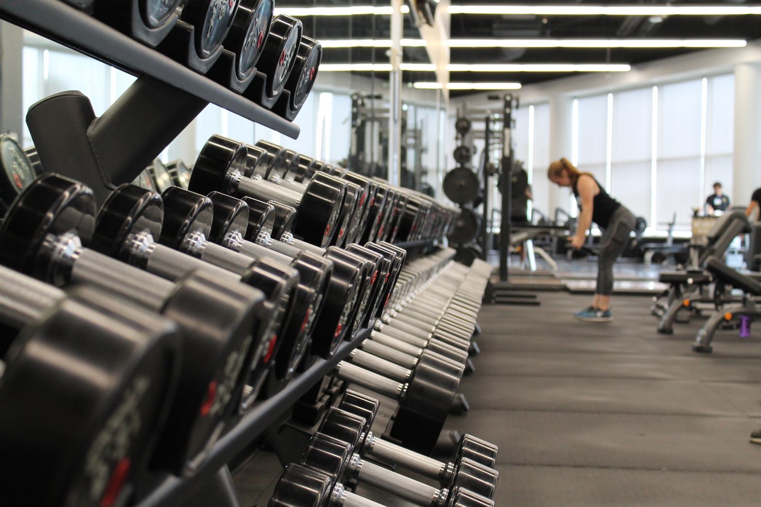row of free weights with a woman at the end of the row