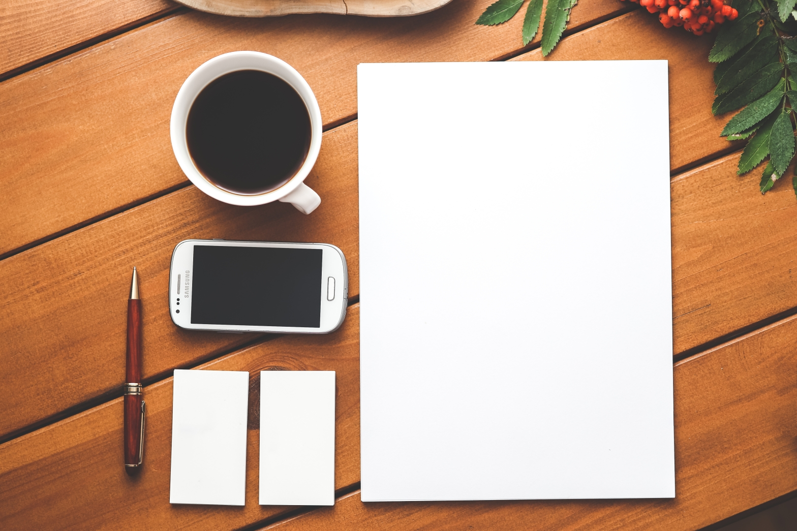 a top-down photo of a blank pad of paper, a couple of white card stacks, a cell phone, a cup of coffee, and a pen.