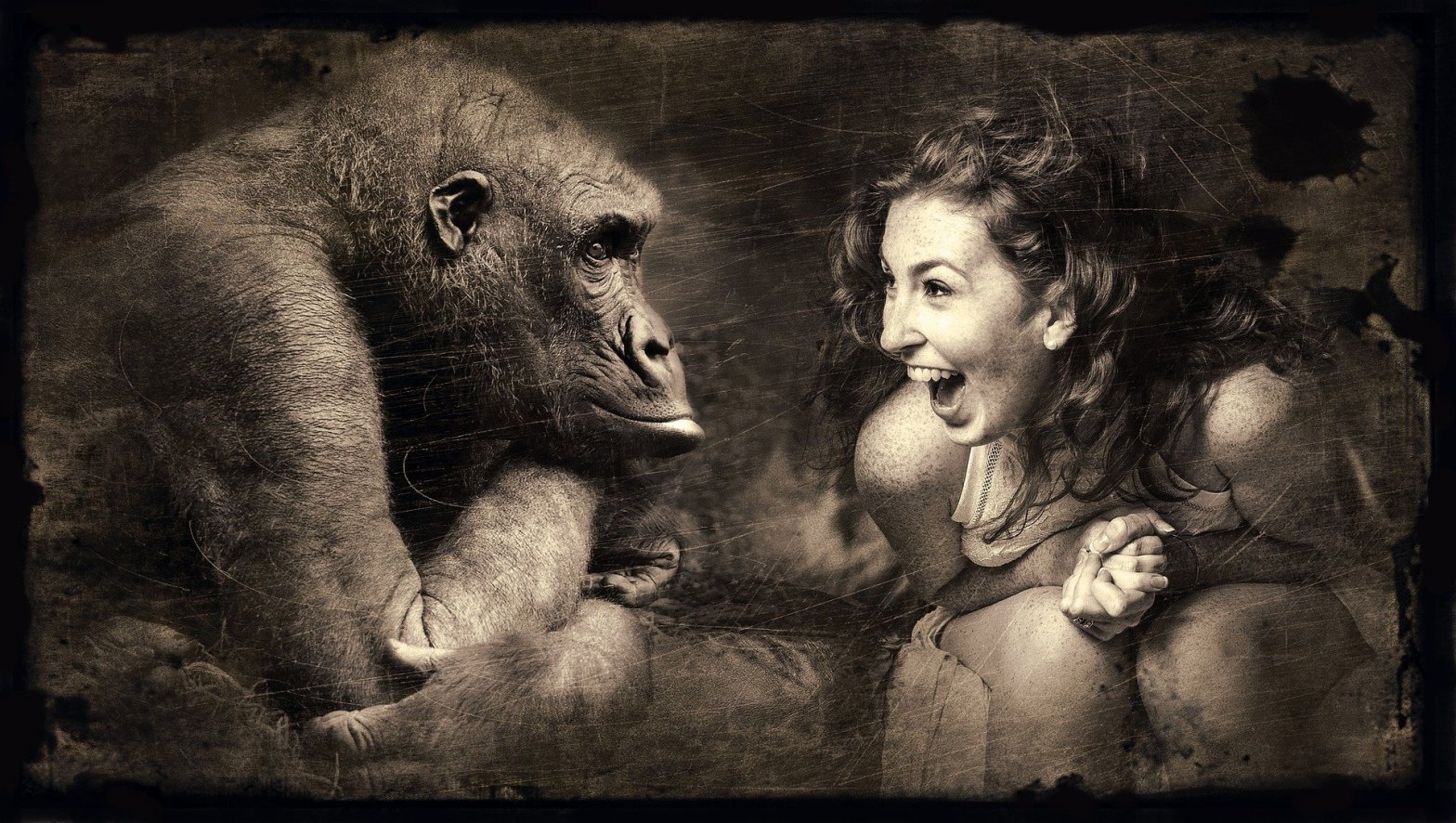 woman looking at a monkey, laughing in delight.